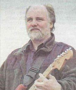 A picture of Steve Thompson songwriter and produce holding a red Fender Stratocaster